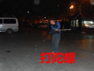 真剣にコマまわしをする中国人