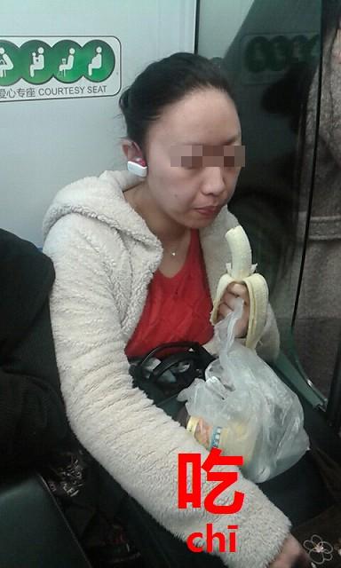 地下鉄で食べる女性