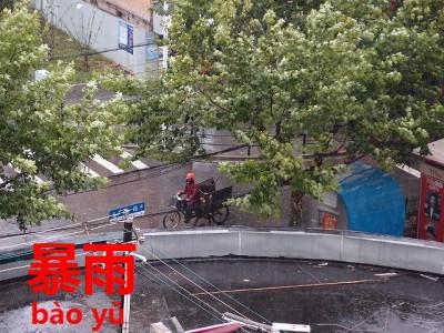 台風襲来した上海の走るバイク