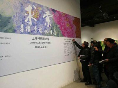 展示パネルにサインをする中国人