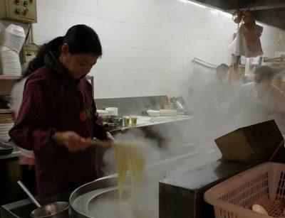 麺を茹でるマダム